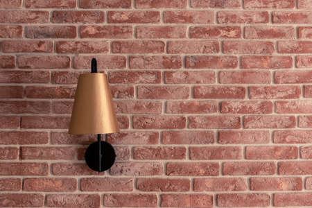 Stylish lamp installed on brick wall against brown curtain