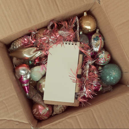 An open cardboard box with old glass Christmas decorations. On top of a clean notepad with a ball pen, copyspace. Standard-Bild