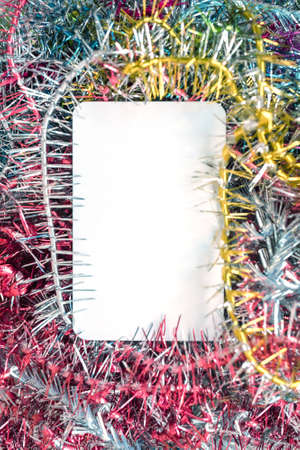 Greeting card with multicolored tinsel frame and white blank card for your text Standard-Bild