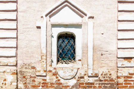 Arch window with white frame and grid in historical building