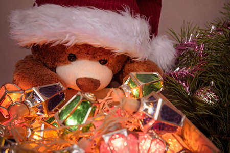 Greeting card with Teddy bear, christmas decor and fairy lights garland.
