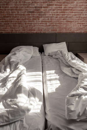 Loft style of bedroom, unmade beds with blankets Standard-Bild