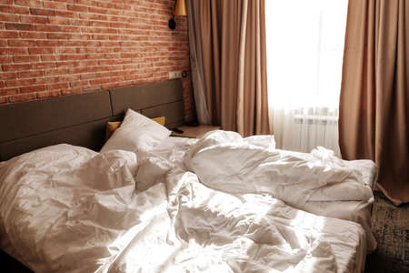 Loft style of bedroom, unmade beds with blankets at the windows. Standard-Bild