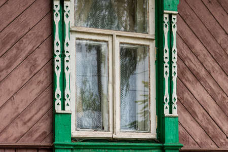 Facade of Russian rural house with platbands on windows in summer sunny day