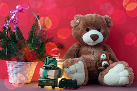 Greeting xmas card with Teddy bear, gift box on toy locomotive.