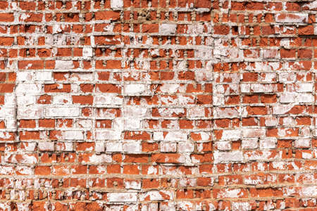 Abandoned building wall with red bricks covered with stucco