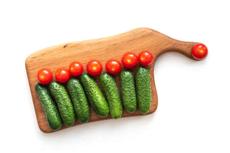 Creative flat lay layout of fresh vegetables cucumbers and tomatoes on wooden board on white Standard-Bild