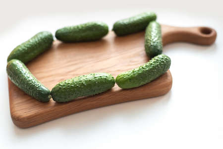 Creative layout of fresh vegetables cucumbers on wooden board on white Standard-Bild