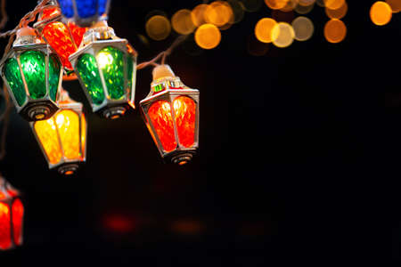 Glowing Xmas lights in black night. colorful Ffairy christmas lights with vintage lantern shaped lamps . Standard-Bild