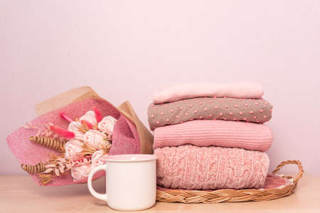 Stack of folded wool knitted sweaters or pullovers in pink pastel colors and mag on table with flowers bouquet Stock fotó