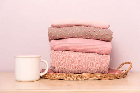 Stack of folded wool knitted sweaters or pullovers in pink pastel colors on table with cup of tea.