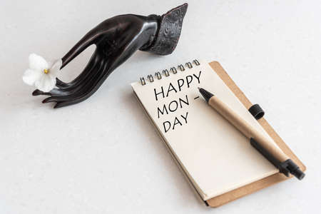 Happy Monday Word in open notebook and flower in black hand. White Office Workplace