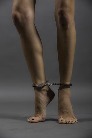 handcuffed female legs, woman on gray background. stutyo work.