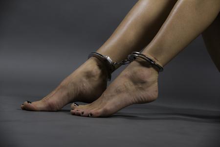 esposado de piernas femeninas, mujer sobre fondo gris. stutyo trabajo.