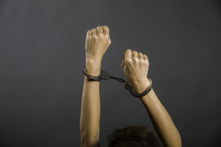 resisting arrest: handcuffed women hands on gray background. stutyo work. program implementation
