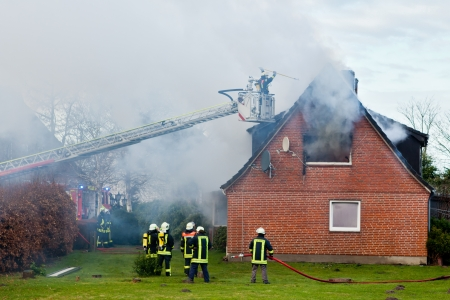 incendio casa: Los bomberos en incendio casa Editorial