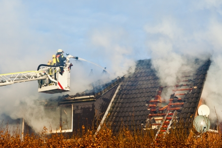 Firefighters on turntable ledder at house fire