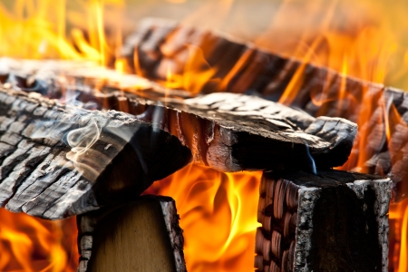 Burning campfire as closeup with flames and wood Standard-Bild