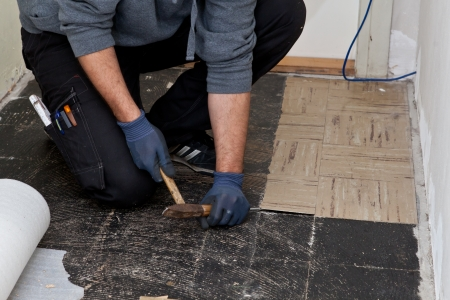 Closeup view of the hands of a builder lifting old floor tiles in a passage using a mallet and chisel during renovations so that he can replace them with new flooring