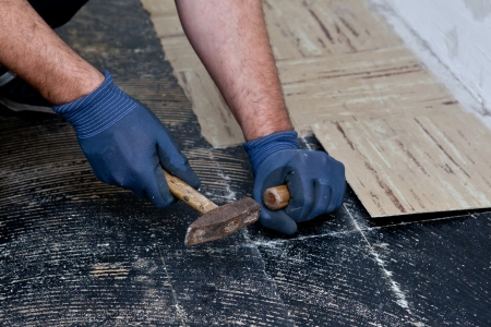 Workman removing old floor tiles using a hammer and chisel during building renovations so that he can install new flooring, close up view of his gloved hands Standard-Bild