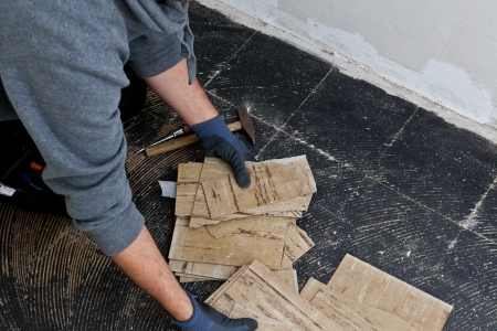 Builder removing damaged floor tiles with his gloved hands during renovations on a building so that he cam install new flooring