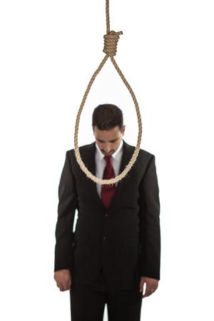 suicidal: Suicidal businessman contemplating hanging standing looking at a hangmans noose