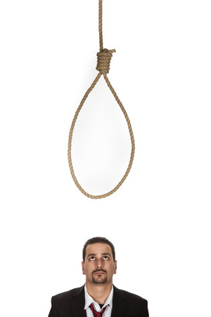 Businessman standing below a hangmans noose contemplating suicide as a result of a business failure or crisis or aware of the punishment for any criminal activity