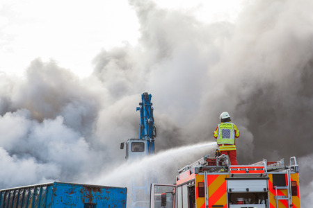Fireman fighting a fire from the top of the truck or fire engine with a fire hose spraying water into a thick billowing cloud of smoke Standard-Bild