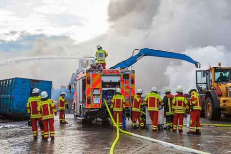 Firefighters attending to a blaze with a fire engine using a fire hose and extended ladder to spray water on the smoke and flames