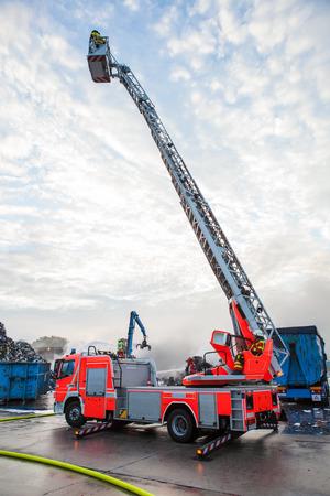 camion grua: Camión de bomberos con una grúa o plataforma elevada y la jaula con la pluma extendida por encima de un fuego ardiente en un sitio industrial Foto de archivo
