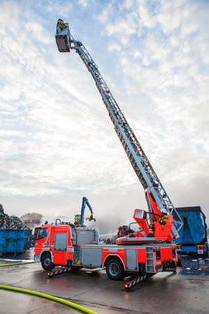 Fire truck with a cherry picker or elevated platform and cage with the boom extended above a smouldering fire on an industrial site Standard-Bild
