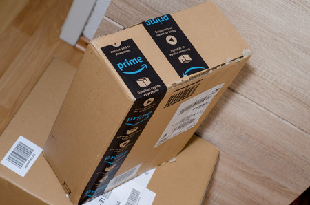 Soest, Germany - December 19, 2017: Amazon Prime logotype printed on cardboard box security scotch tape. Amazon Prime is a paid subscription service offered by Amazon.com. Illustrative editorial. 報道画像