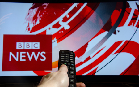 Soest, Germany - January 14, 2018: Man watching BBC News on TV. BBC News is an operational business division of the British Broadcasting Corporation (BBC). Editorial