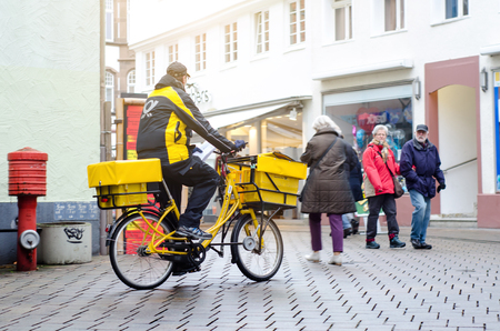 Soest, Germany - January 3, 2019: Deutsche Post postman by bike. The Deutsche Post AG, operating under the trade name Deutsche Post DHL Group.