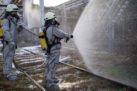 Bomberos en traje de protección química. Foto de archivo