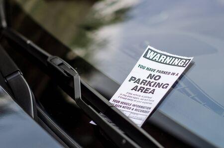 Close-up de ticket de estacionamiento en el parabrisas del coche.