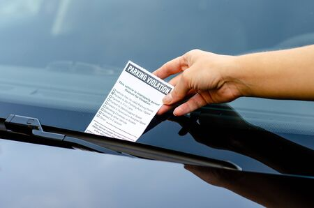 Close-up Of A Woman Taking Parking Ticket On Car's Windshield Archivio Fotografico