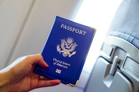 Hand holding U.S. passport inside airplane cabin.
