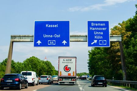 North Rhine-Westphalia, Germany - August 2, 2019: Road traffic on the German autobahn 1 with road signs. Cars ride on the German autobahn.