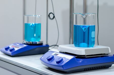 A magnetic stirrer or magnetic mixer is a laboratory device that employs a rotating magnetic field to cause a stir bar immersed in a liquid to spin very quickly, thus stirring it. Stock Photo