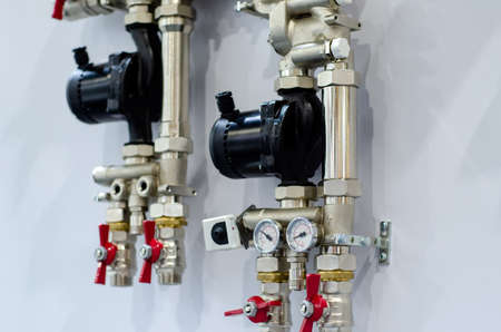 Close up of house heating system with many steel pipes, manometers, pump and metal tubes.