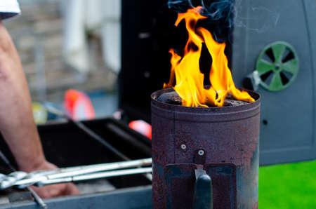 Burning coals for grilling. Charcoal chimney starter