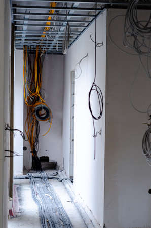 Electric installation work. Pulling wires in an unfinished house Stock fotó
