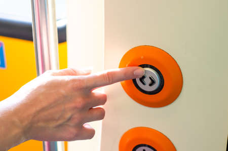 Hand presses the button to open the doors in the train