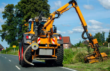 Maintenance of the edge of a road by a brush cutter tractor. Stock fotó