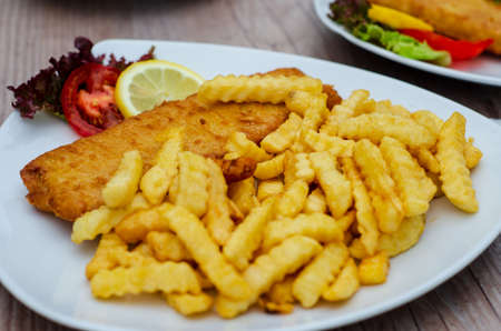 Batter fish with french fries and fresh vegetables Stock fotó