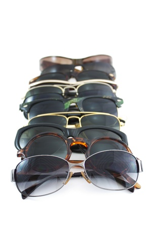 several pile up sunglasses on white background photo