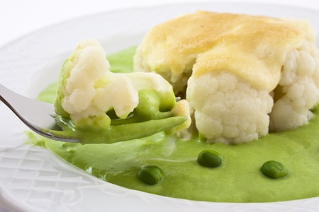 baked cauliflower cheese and pea cream. A portion of cauliflower with pea sauce in the fork photo