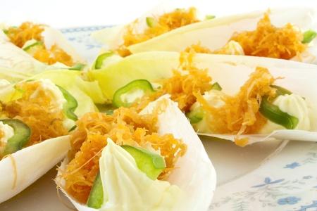 endivia: hojas de endivia con mayonesa, zanahoria rallada y pimiento verde Foto de archivo