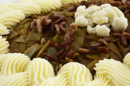 creamed: green beans with bacon and creamed potatoes on ceramics plate and decorated with cauliflower Stock Photo